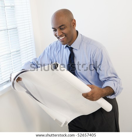 African American businessman reading architectural plans and smiling. - stock photo