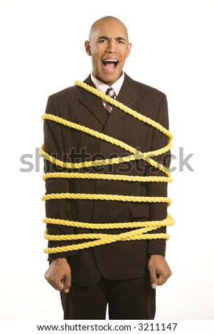 African American businessman screaming wrapped in yellow rope. - stock photo
