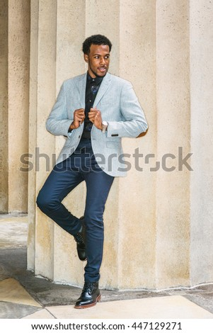African American Businessman Semi-Formal Fashion in New York. Wearing gray blazer, unbuttoned,  blue pants, black leather boot shoes, a guy standing against columns outside office, looking away.  - stock photo
