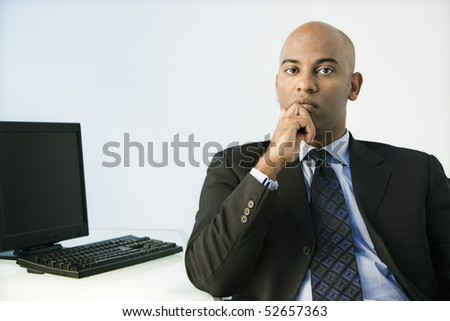 African American businessman sitting at office desk. - stock photo