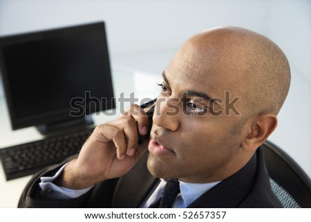 African American businessman sitting at office desk on cellphone. - stock photo