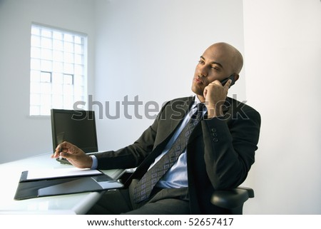 African American businessman sitting at office desk talking on cellphone. - stock photo