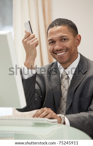 African American businessman sitting at the computer in his office holding up his credit card - stock photo