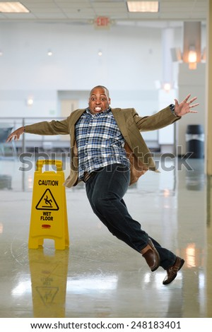 African American businessman slipping on wet floor inside office building - stock photo