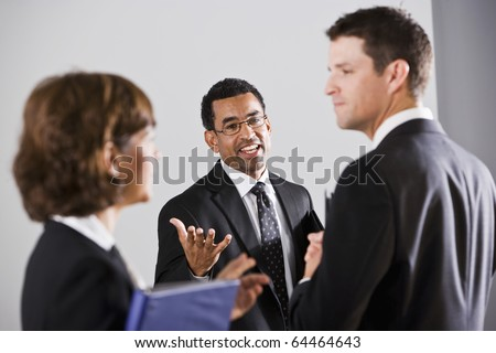 African American businessman, 40, talking with two colleagues