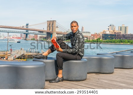 African American businessman traveling in New York. Wearing black flower patterned shirt, tie, shoes, a young guy sitting at harbor, reading red book. Manhattan, Brooklyn bridges, boats on background.