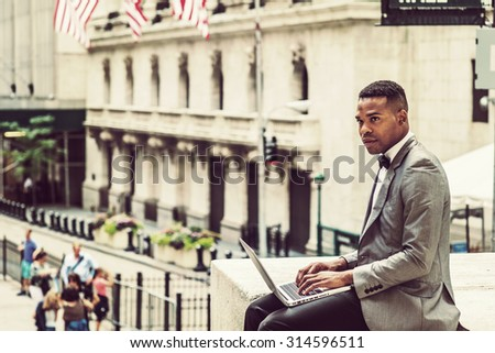 African American Businessman traveling, working in New York. Wearing gray blazer, bow tie, a young black man siting on street, looking around, reading, working on laptop computer. Instagram effect.  - stock photo