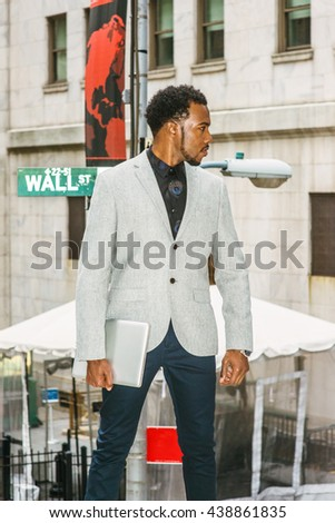 African American Businessman traveling, working in New York. Wearing gray blazer, holding laptop computer, a black man with beard standing on street, looking forward, confident, successful.