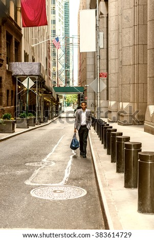African American Businessman traveling, working in New York. Young black man walking on narrow old street with high buildings, carrying blue bag, wearing blazer, shirts. Color filtered effect.  - stock photo