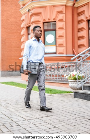 African American businessman with briefcase on a background of red buildings in the city
