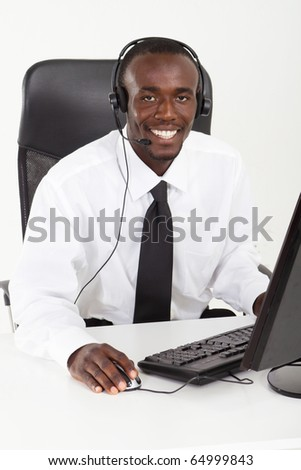 African American businessman with headset sitting at office desk - stock photo