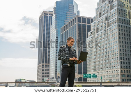 African American businessman working in New York. Wearing black flower patterned shirt, tie, a young guy standing in front of business district, reading, typing, working on laptop computer.  - stock photo