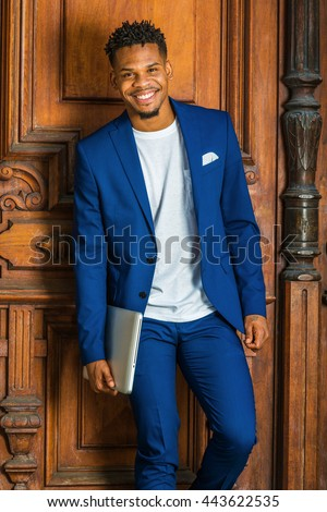 African American Businessman working in New York. Wearing blue suit, white T shirt, college student with little goatee, standing by vintage library door on campus, carrying laptop computer, smiling.  - stock photo