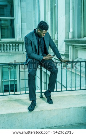 African American Businessman working in New York. Wearing fashionable jacket, necktie, a young guy sitting on railing, looking down, checking messages on cell phone. Filtered look with cyan tint.