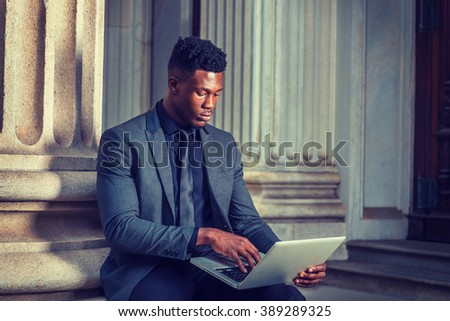 African American Businessman working in New York. Wearing fashionable jacket, necktie, young black man sitting outside office building, typing, working on laptop computer. Instagram filtered effect. - stock photo