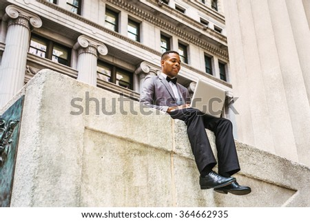 African American businessman working in New York, wearing gray blazer, bow tie, black pants, leather shoes, siting on street, reading, working on laptop computer, thinking. Instagram filtered effect.  - stock photo