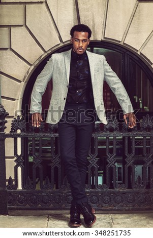 African American Businessman working in New York, wearing gray blazer, flower patterned undershirt, pants, leather boot shoes, standing by railing, tensely looking at you. Instagram filtered look. - stock photo
