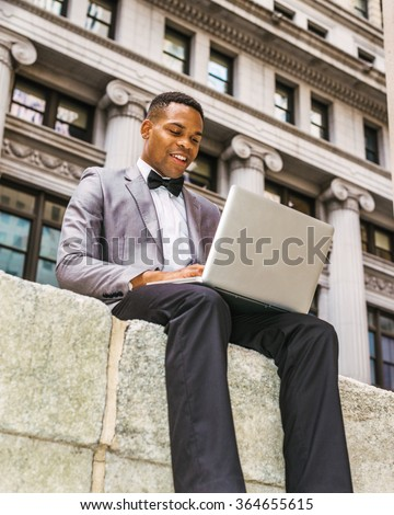 African American businessman working on street in New York. Wearing gray blazer, bow tie, young black man siting in business district, reading, working on laptop computer. Instagram filtered effect.  - stock photo
