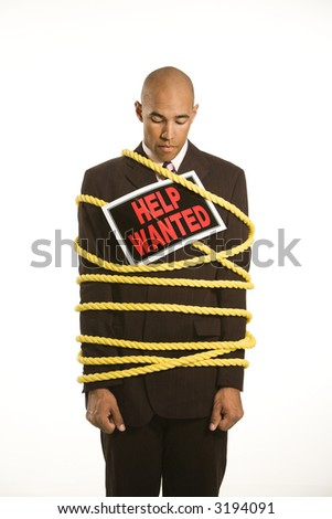 African American businessman wrapped in yellow rope wearing help wanted sign. - stock photo