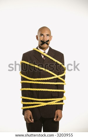 African American businessman wrapped in yellow rope with tape over  his mouth. - stock photo