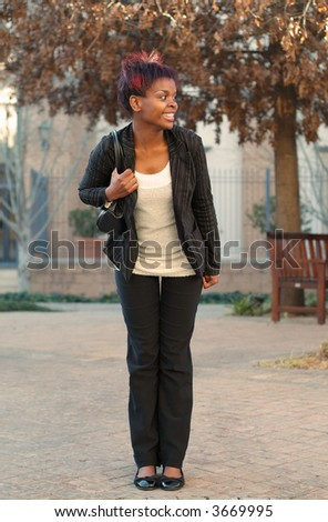 African American businesswoman commuter waiting for bus at stop - stock photo