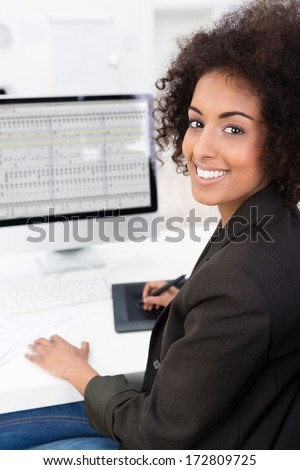 African American businesswoman doing a spreadsheet using a tablet and stylus with her desktop computer turning to smile at the camera - stock photo