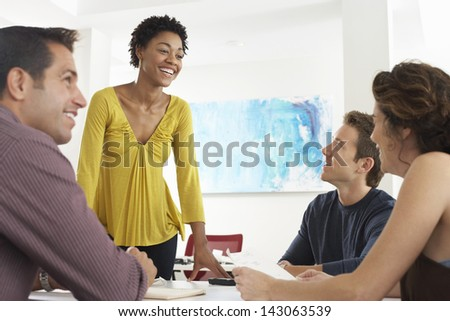 African American businesswoman having discussion with colleagues in office - stock photo