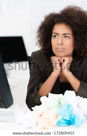African American businesswoman in trouble suffering from writers block or lack of imagination in solving a business problem surrounded by a heap of crumpled paper - stock photo