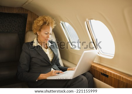African American businesswoman on airplane - stock photo