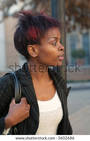 African American businesswoman portrait - looking to the left while waiting for public transport bus at stop - stock photo
