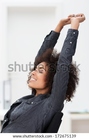 African American businesswoman relaxing at work reclining back in her chair stretching her arms in the air and closing her eyes in contentment - stock photo