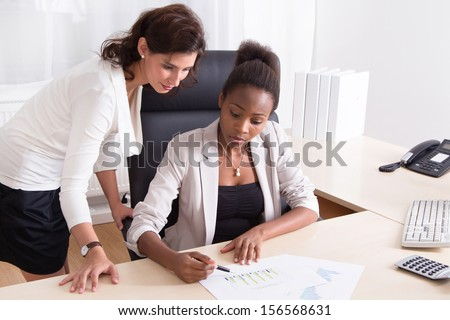 African American businesswoman showing chart to her Caucasian colleague.  - stock photo