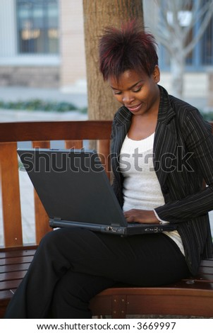 African American businesswoman sitting on outside bench with laptop - stock photo