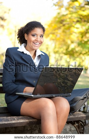 African American businesswoman  with laptop, looking in camera and smiling