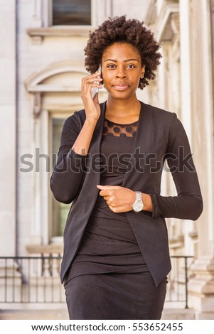African American Businesswoman with short afro hairstyle working in New York, wearing fashionable work clothes, wristwatch, stands in office building, talking on cell phone. Color filtered effect