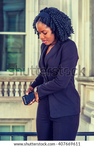 African American Businesswoman working in New York. Dressing in black, female professional with braid hairstyle standing by office building, taking out cell phone from pocket, hurry to answer a call.