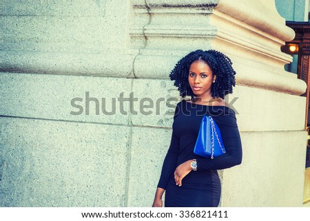 African American Businesswoman working in New York. Wearing long sleeve, slim off shoulder dress, carrying blue bag under arm, young black lady with braid hairstyle standing on street, looking at you. - stock photo