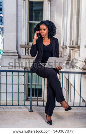 African American Businesswoman working in New York. Young black college student sitting on railing in office building, working on laptop computer, making phone call. Filtered look with dark blue tint. - stock photo