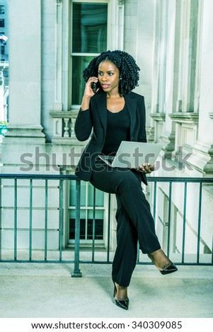 African American Businesswoman working in New York. Young black college student sitting on railing in office building, working on laptop computer, making phone call. Filtered look with green tint. - stock photo