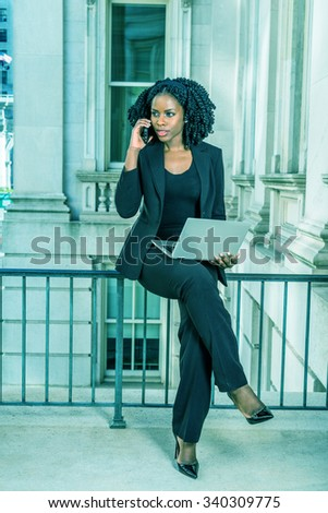 African American Businesswoman working in New York. Young black college student with braid hairstyle sitting on railing, working on laptop computer, making phone call. Filtered look with cyan tint. - stock photo