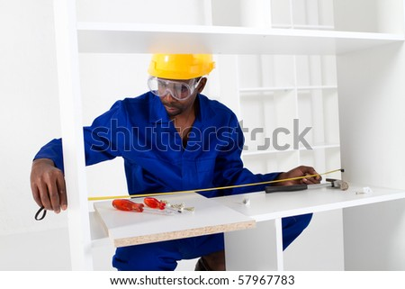 african american carpenter assembly furniture - stock photo