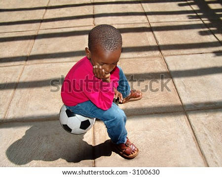 African American child sitting on the ball waiting for his friends at school for a soccer game. - stock photo