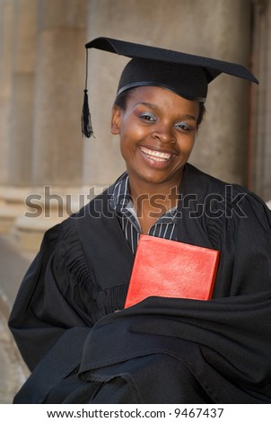 African American college student graduating with mortarboard and book - stock photo