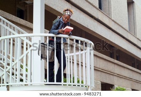 African American college student on campus staircase with building background. - stock photo
