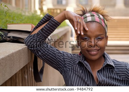 African American college student on campus with book and bag - stock photo