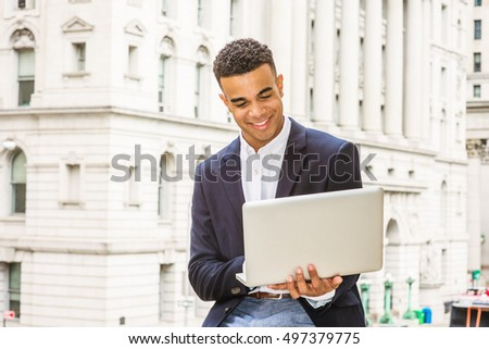 African American college student studies in New York.  Wearing black blazer, young happy guy sits on street by vintage office building on campus, reads, works on laptop computer. Filtered effect.
