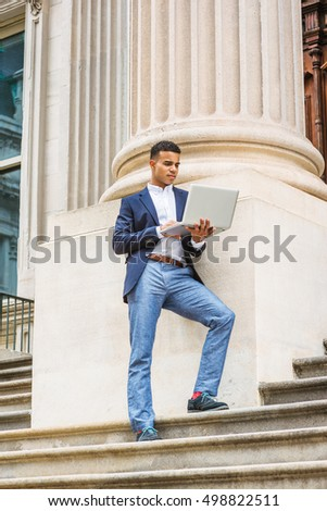 African American college student studies in New York. Wearing blue blazer, white shirt, gray pants, sneakers, man stands on stairs against column outside office building, works on laptop computer.