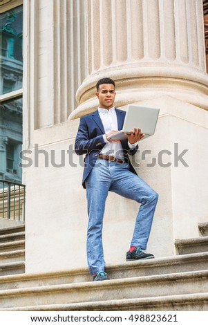 African American college student studies in New York. Wearing blue blazer, white shirt, gray pants, sneakers, young stands on stairs against column outside office building, works on laptop computer.