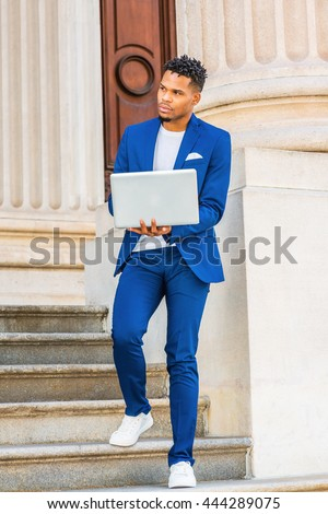 African American college student studying in New York, wearing blue suit, white sneakers, standing on stairs of vintage office building on campus, working on laptop computer, looking away, thinking. - stock photo