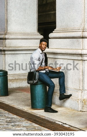 African American College Student studying in New York, wearing shirt, jeans, carrying shoulder leather bag, sitting on pillar on street, reading, working on laptop computer. Instagram filtered effect  - stock photo